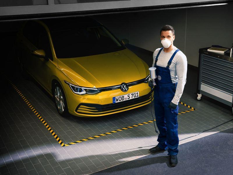 Un addetto all'igienizzazione dell'auto in un centro Volkswagen Service.