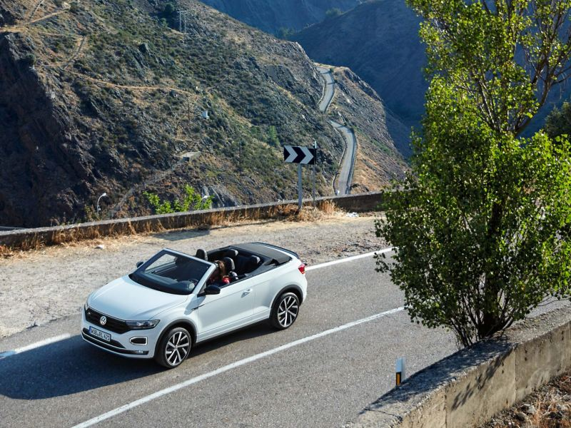A silver VW Tiguan from replacement vehicle service drives on a road by the sea