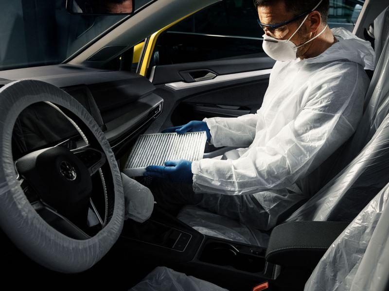 Un tecnico di Volkswagen Service all'interno di un veicolo mentre controlla i filtri aria dell'abitacolo.