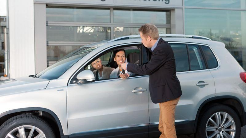 Händler übergibt Schlüssel an Paar in Auto