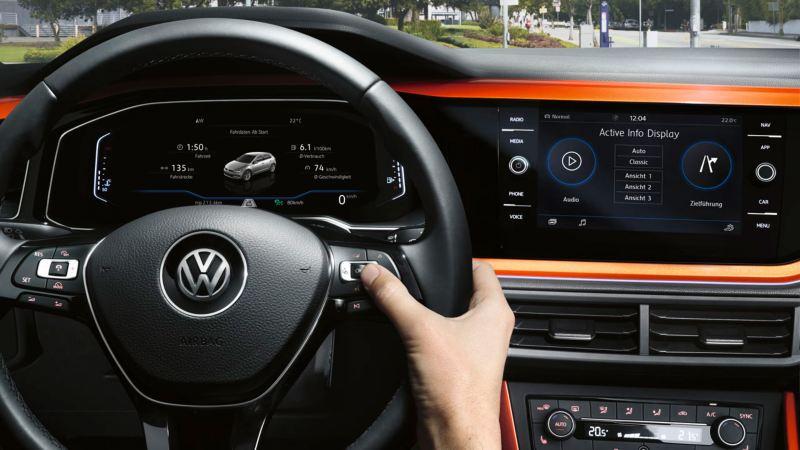 Mano sujetando el volante de un Volkswagen Polo naranja