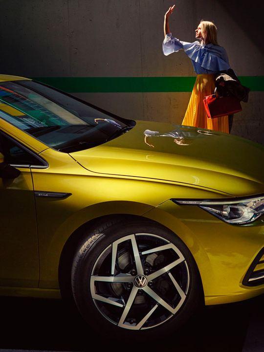 Vista lateral de un Volkswagen Golf amarillo aparcado