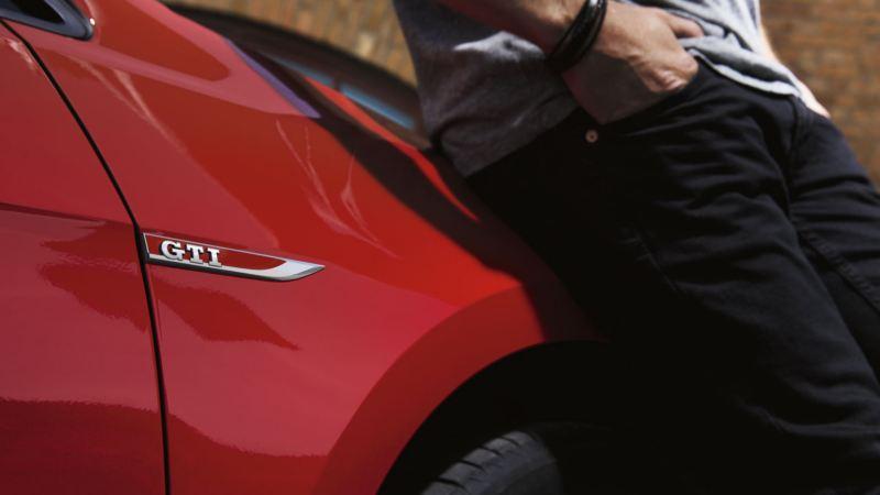 Embellecedor de un Golf GTI rojo junto a un chico apoyándose con las manos en los bolsillos