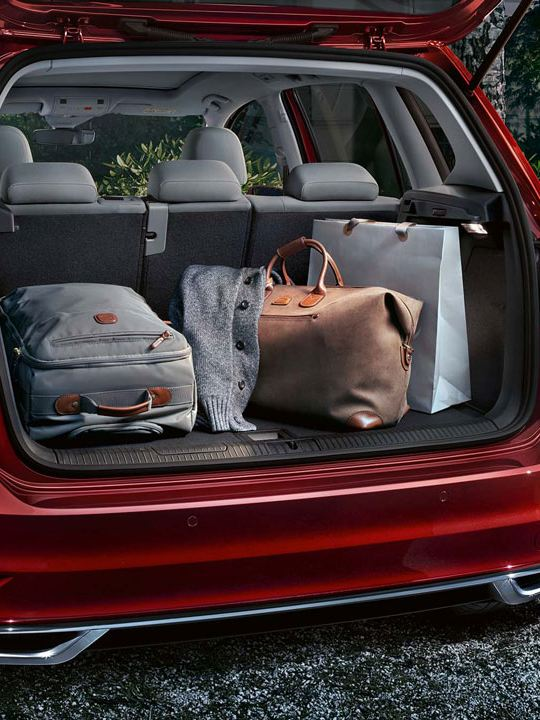 Maletero lleno de un Golf Sportsvan rojo aparcado tras una casa por la noche