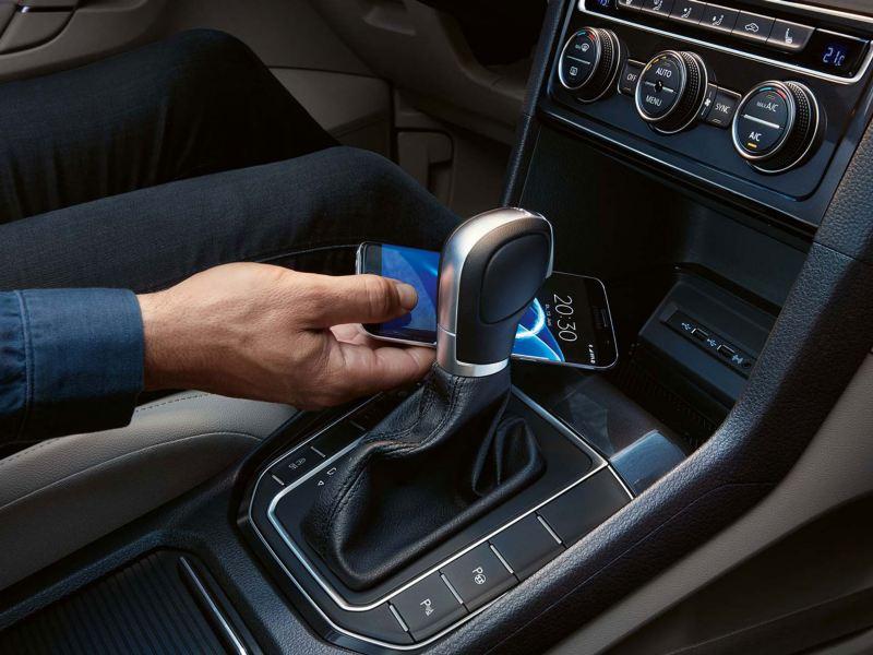 Mano dejando un móvil en el soporte de un Golf Sportsvan