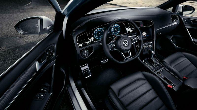 Interior frontal de un Golf Variant tapizado en negro visto desde de ventanilla del conductor