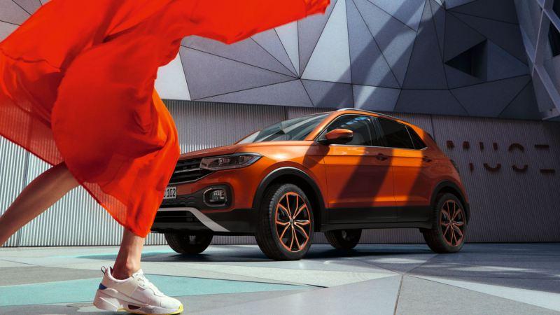 T-Cross naranja calatea aparcado en la calle junto a una chica bailando