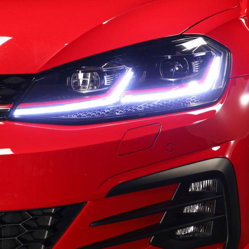 Faros LED encendidos de un Golf GTI rojo