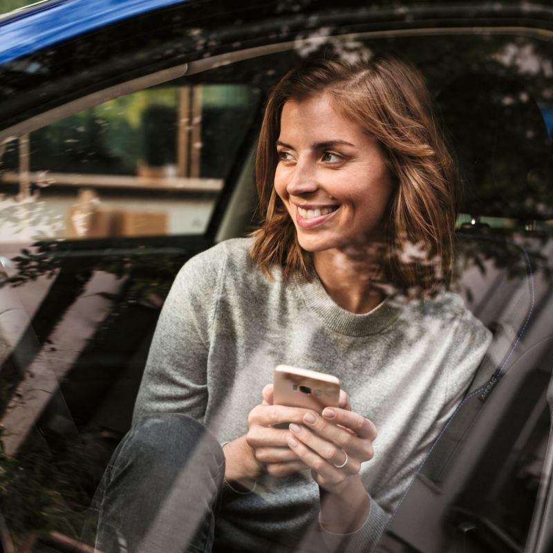 Chica sentada en el asiento de su Volkswagen mientras mira el móvil y sonríe