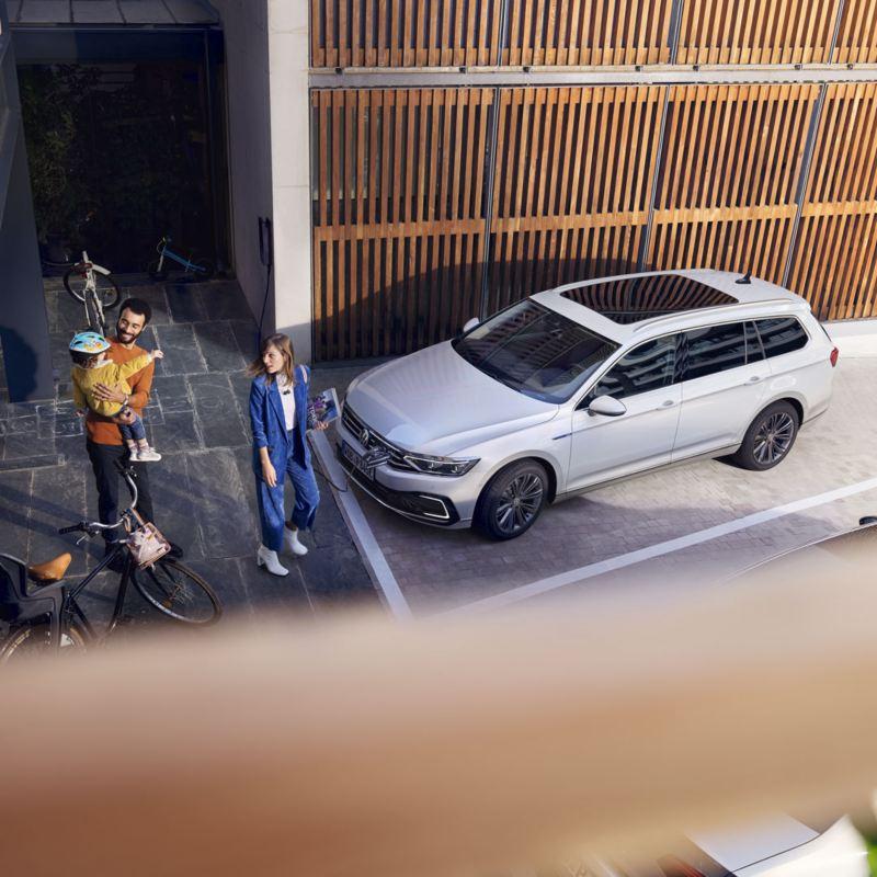 Vista superior de una familia delante de un Volkswagen Passat GTE Variant