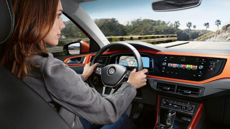 Chica mirando a la carretera mientras conduce un Volkswagen Polo naranja