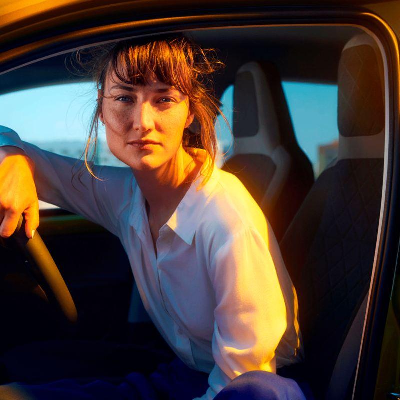 Mujer joven al volante de un e-up! mirando de forma directa a la cámara