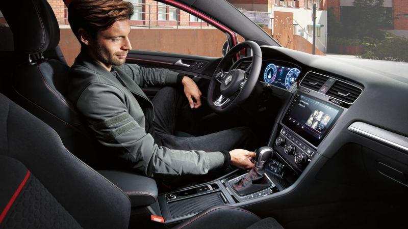 Hombre dejando su móvil en el soporte de un Golf GTI con la puerta abierta