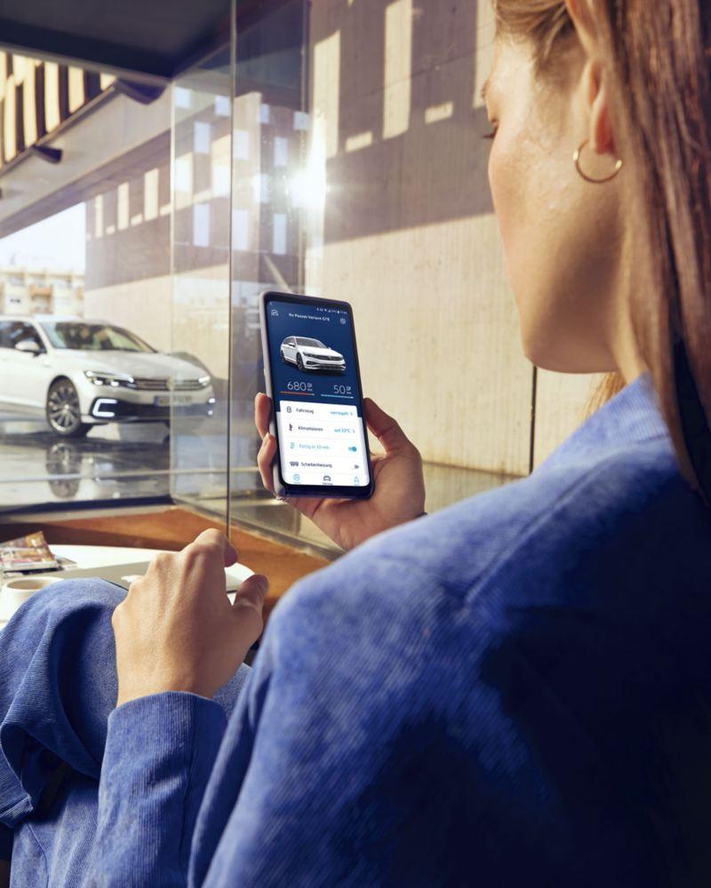 Mujer con smartphone conectada al Volkswagen Passat GTE con e-Remote