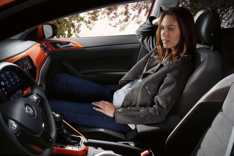 Chica sentada de forma relajada en el asiento del copiloto de un Volkswagen Polo
