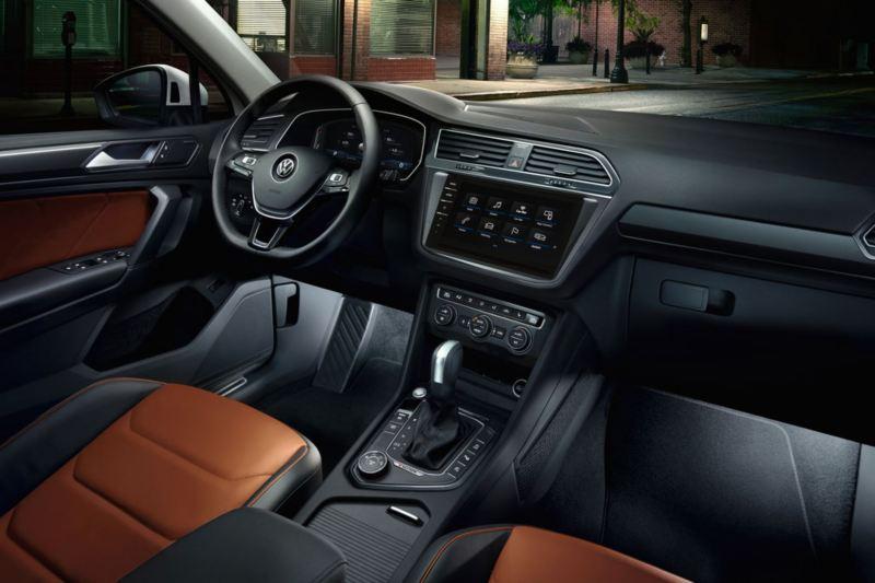 Vista del puesto de conducción y la iluminación interior de un Volkswagen Tiguan de noche en la ciudad