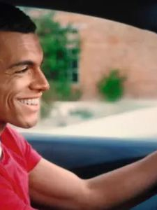 A smiling young man in a red shirt behind the wheel of a Volkswagen ID.3, passenger side view