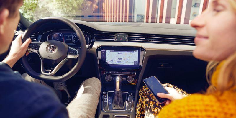 Hombre joven en el puesto de conducción del Volkswagen Passat Variant, mujer joven sostiene un móvil. En la pantalla se ve el navegador