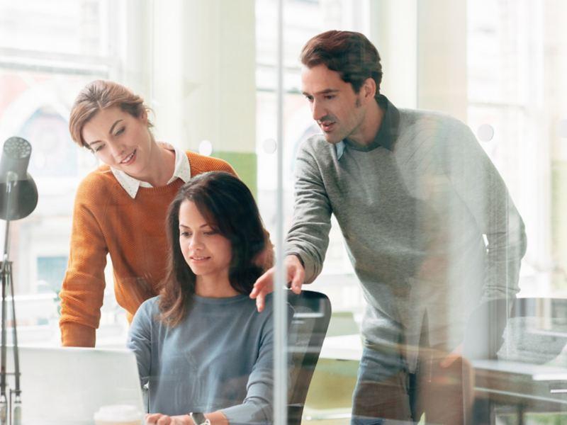 Eine Frau arbeitet am Laptop, zwei Kollegen schauen ihr über die Schulter