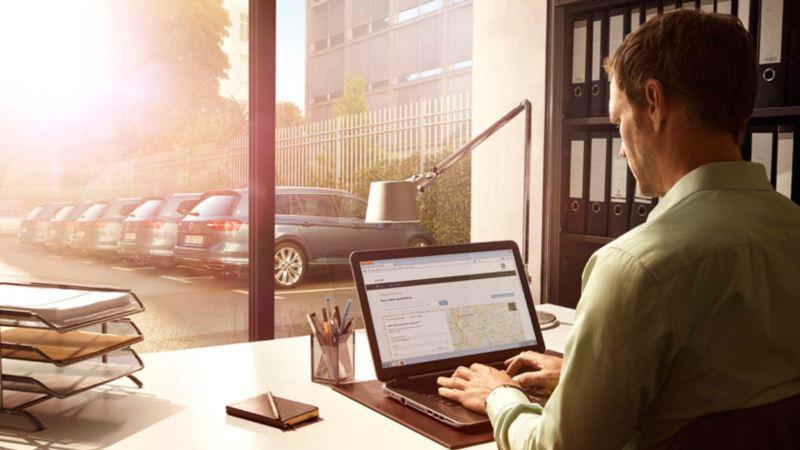 Un uomo seduto a un tavolo consulta sul suo computer la mappa delle concessionarie Volkswagen.