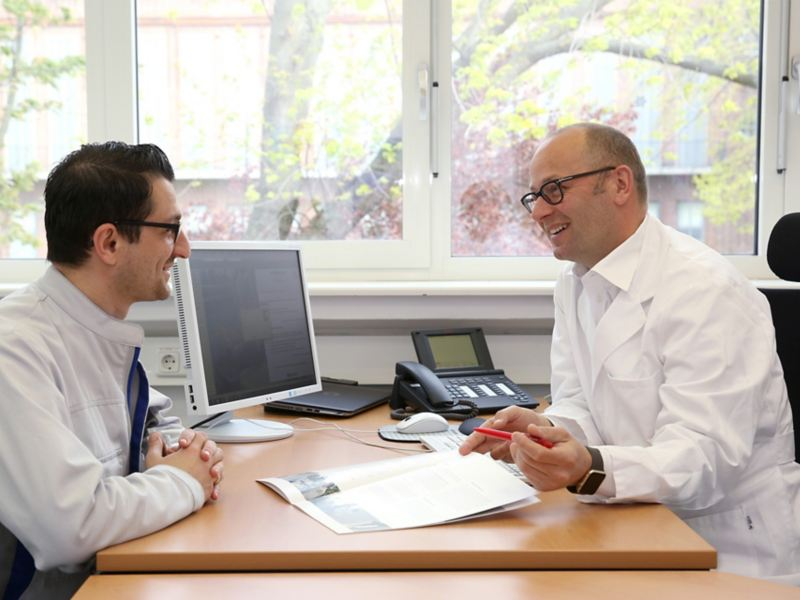 Zwei Männer sitzen sich an einem Schreibtisch gegenüber