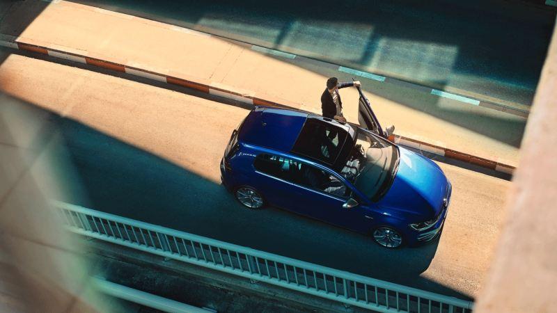 Vista superior del Volkswagen Golf aparcado en la calle y un hombre joven con la puerta abierta