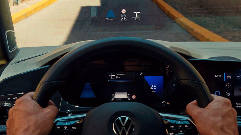 Detalle de la pantalla de visualización frontal vista a través de un volante cogido por dos manos