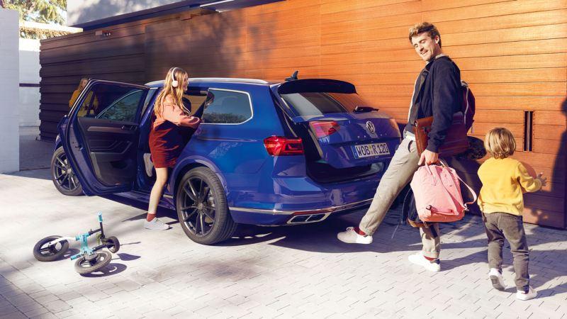 Familia subiendo a un Volkswagen Passat Variant azul, el padre abre el portón trasero con un movimiento de pié