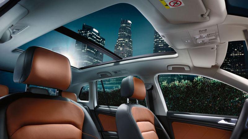 Vista interior del techo solar panorámico del Volkswagen Tiguan de noche en la ciudad