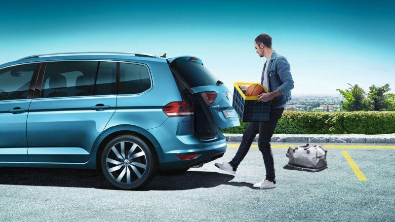 Vista lateral de un Touran azul con un chico abriendo su maletero con un movimiento de pie