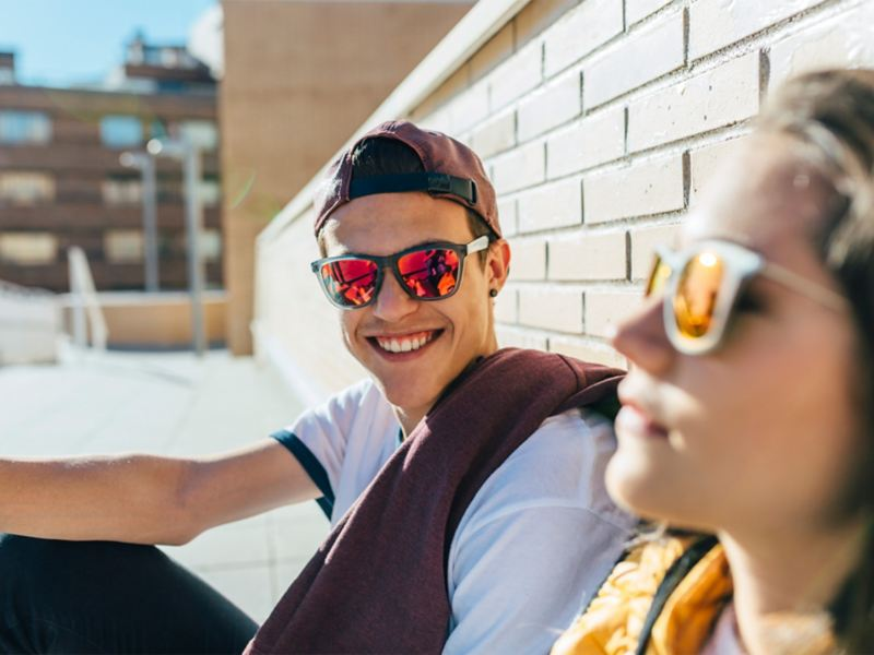 A young woman and a young man outdoors wearing sunglasses