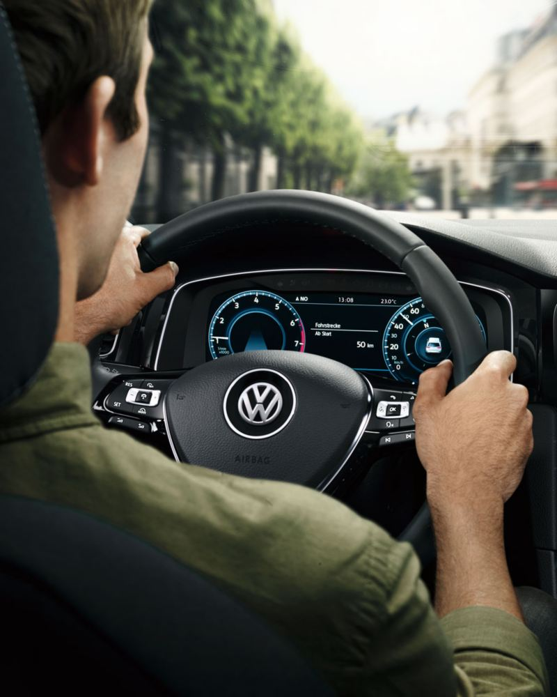 Hombre joven conduciendo un Volkswagen Golf, vista del Digital Cockpit