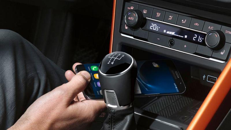 Mano dejando un móvil en el soporte delantero de un Volkswagen Polo naranja