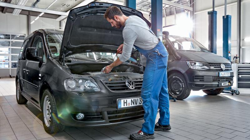 Un addetto di Volkswagen Service mentre lavora sul motore di un veicolo.