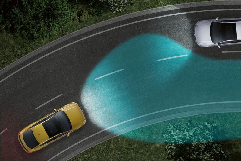 Una Volkswagen di notte su una strada vista dall'alto. Si vede la regolazione degli abbaglianti come cono di luce