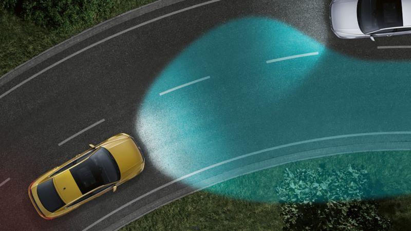 Una Volkswagen di notte vista dall'alto mentre affronta una curva. Si vedono le luci di svolta dinamiche come cono di luce