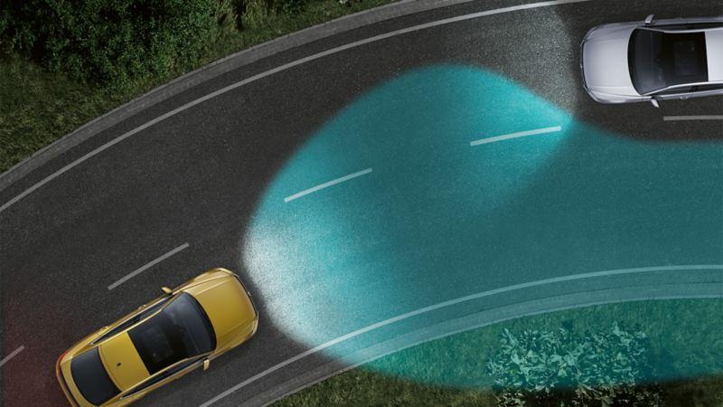 Volkswagen nocą widziany od góry na zakręcie. Widać światła doświetlające zakręty jako stożek światła