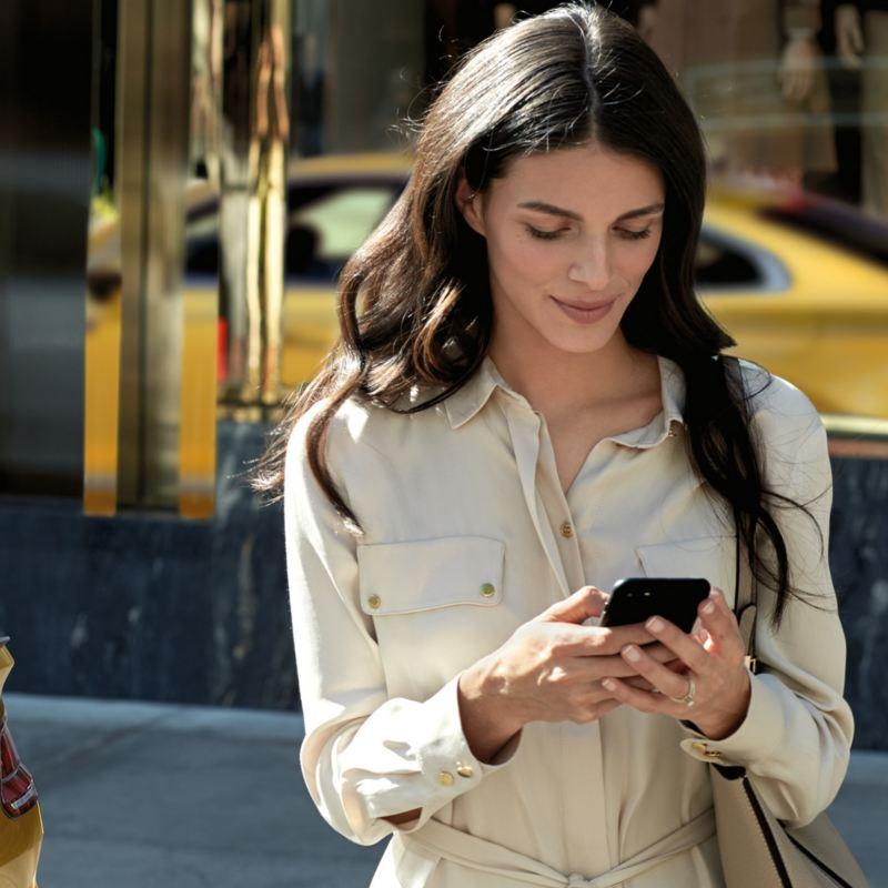 donna sorridente digita sul cellulare dietro Arteon gialla