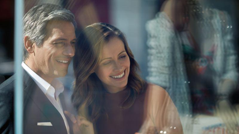 Coppia felice che guarda una vetrina - VW Veicoli Commerciali