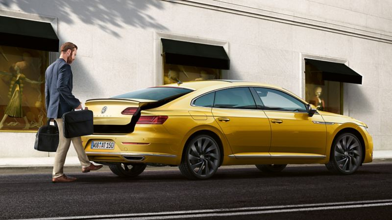 A man opens the luggage compartment of the VW Arteon R-Line using the foot sensor system
