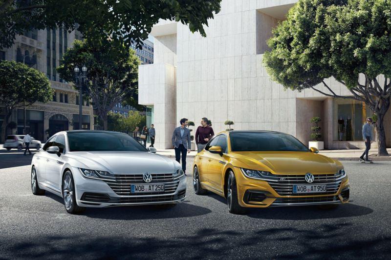 Kaksi Volkswagen Arteon autoa etuviistosta kuvattuna parkissa kaupungin keskustassa. Taustalla kaksi ihmistä keskustelemassa
