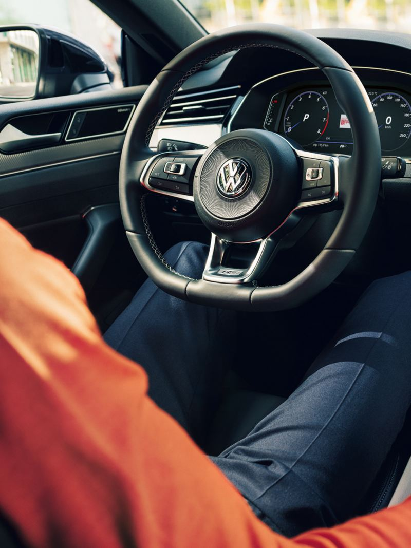 Mann mit Smartphone im Cockpit des VW Arteon R-Line Edition