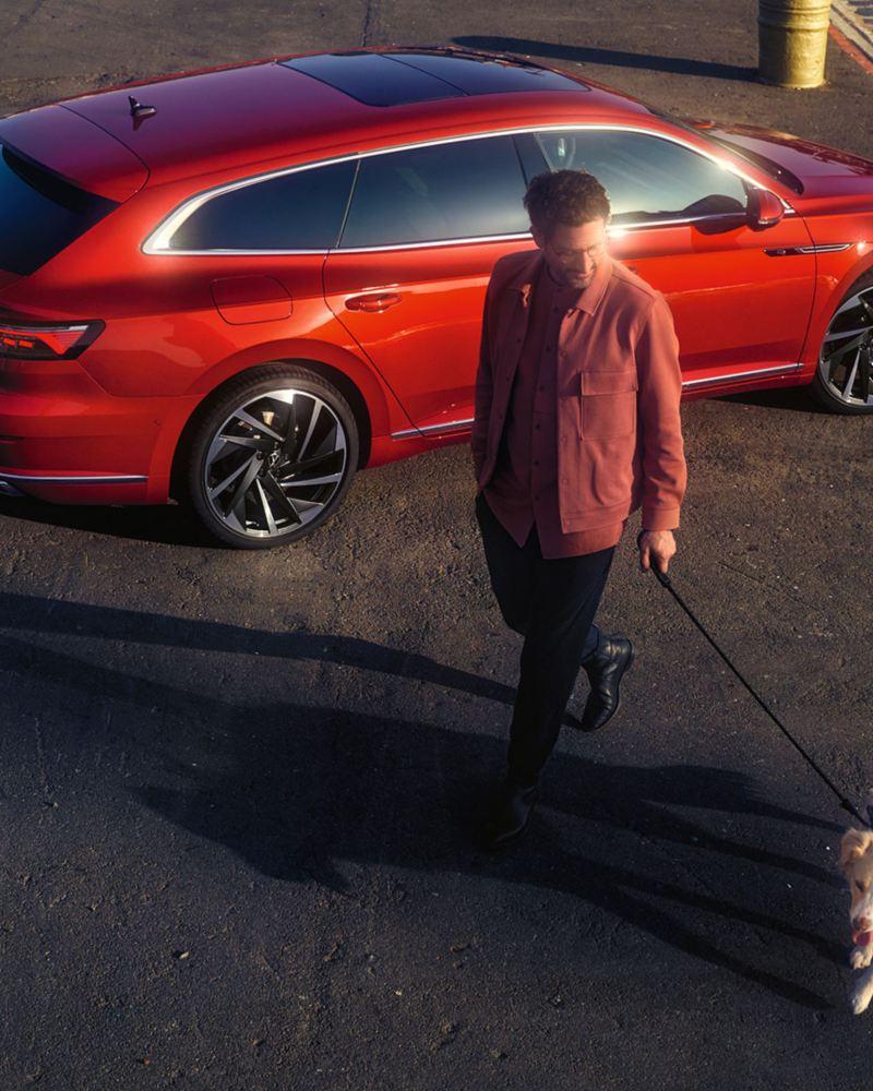 Um homem passeia o cão perto do novo Volkswagen Arteon Shooting Brake