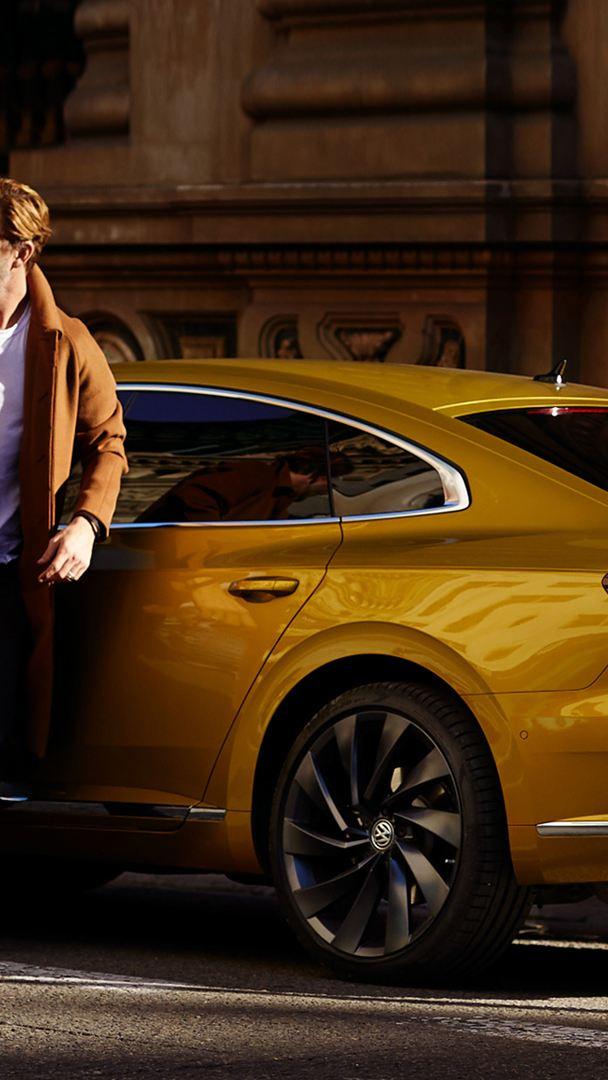 uomo chiude sportello auto gialla