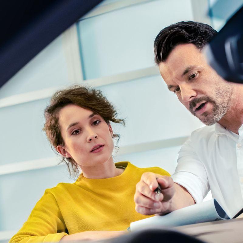 Frau und Volkswagenmitarbeiter im Beratungsgespräch – Finanzierungsratgeber