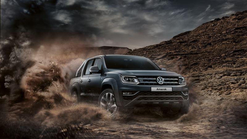 vw Volkswagen Amarok pickup service- og vedlikeholdsavtale 4x4 4motion offroad kjører og sladder i grus omgitt av støvsky