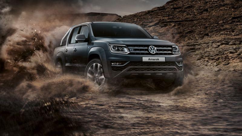 vw Volkswagen Amarok pickup 4x4 4motion offroad kjører og sladder i grus omgitt av støvsky