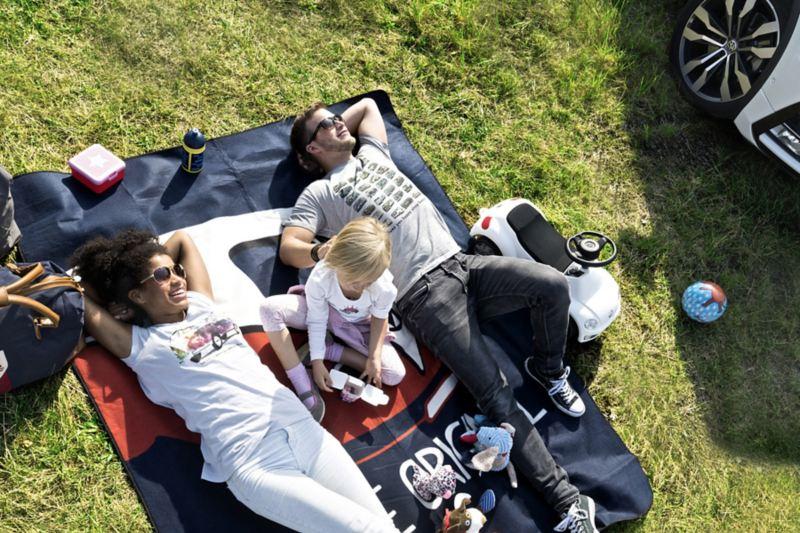 Eine Familie liegt auf einer Wiese und entspannt