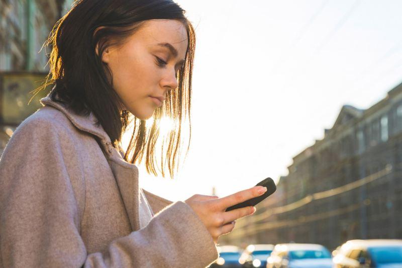 Frau sucht auf dem Handy nach einer Ladestation.
