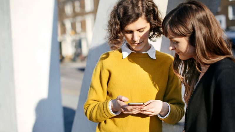 Due donne guardano insieme uno smartphone.